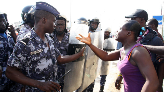 A woman confronts police officers outside a gathering in Lome, Togo, of the opposition group Let's Save Togo.