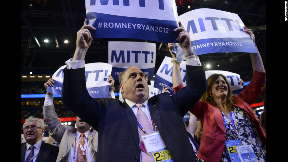 Supporters flash posters supporting Republican presidential candidate Mitt Romney at the Tampa Bay Times Forum.