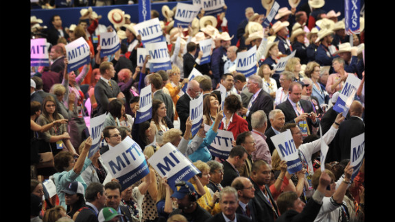 Delegates display signs in support of Mitt Romney after the tallying of votes during the roll call for nomination of president of the United States.