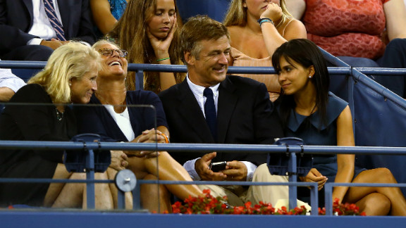 Alec Baldwin, center, and his wife, Hilaria Thomas, right, watch the first day of action Monday at the U.S. Open.