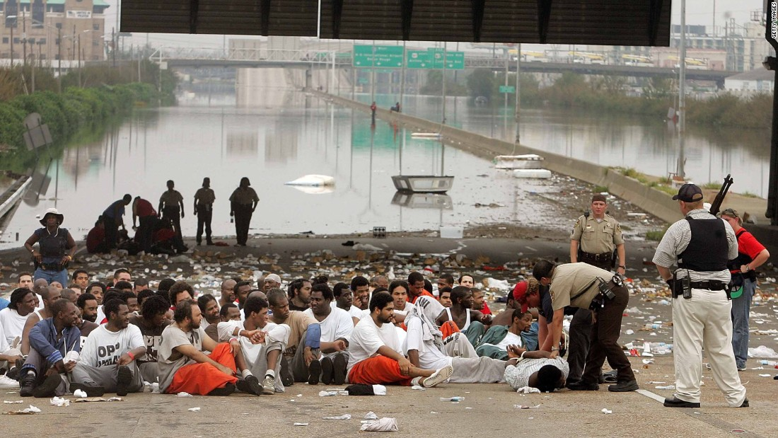 Police watch over prisoners from Orleans Parish Prison who were evacuated to a highway on September 1, 2005.