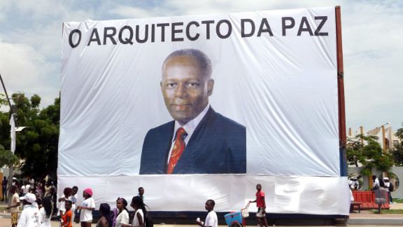 """Earlier this year, Angola celebrated 10 years of the end of its civil war. Here, Luanda residents walk in front of a giant portrait of President  dos Santos, with text reading """"The Architect of Peace"""" on April 4, 2012."""