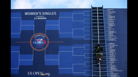 A worker climbs a ladder to adjust the board displaying the women