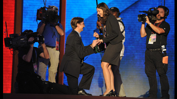 Bradley Thompson kneels down to propose to Laura Bowman, who accepted, on the stage.