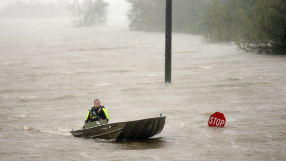 A rescue boat passes a partially submerged stop sign.