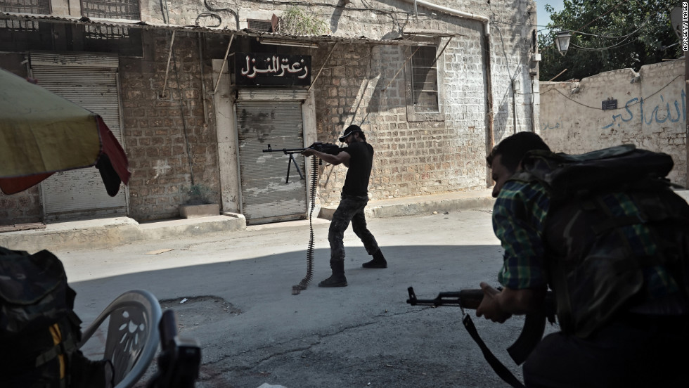 An opposition fighter fires at government forces from a street in Aleppo.