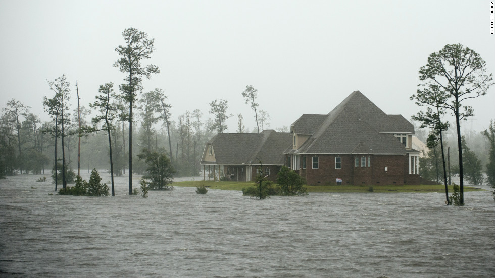 Water surrounds a home on the Jourdan River in Kiln, Mississippi, as Isaac moves through the area.