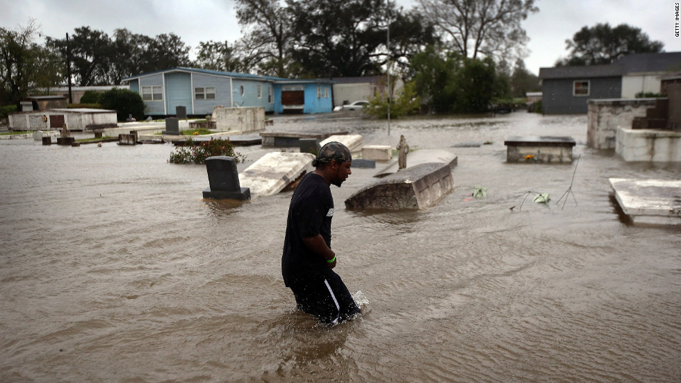 Errol Ragas walks past a cemetery to recover dry blankets from his home as rising waters flood in Oakville, Louisiana. Plaquemines Parish, south of New Orleans, was the area most heavily damaged by the hurricane.