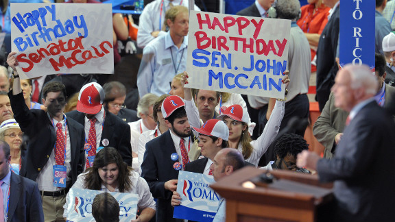 As Sen. John McCain speaks, some audience members display happy birthday posters.