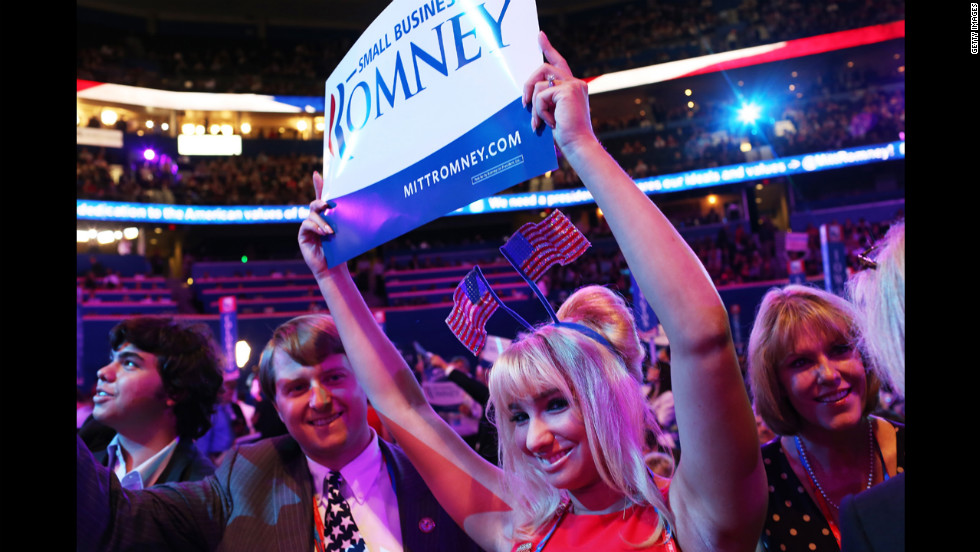 A woman holds a campaign sign.