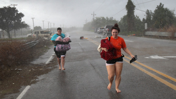 Residents run down a road in Slidell clutching their belongings as they evacuate an area of rising floodwaters from Isaac