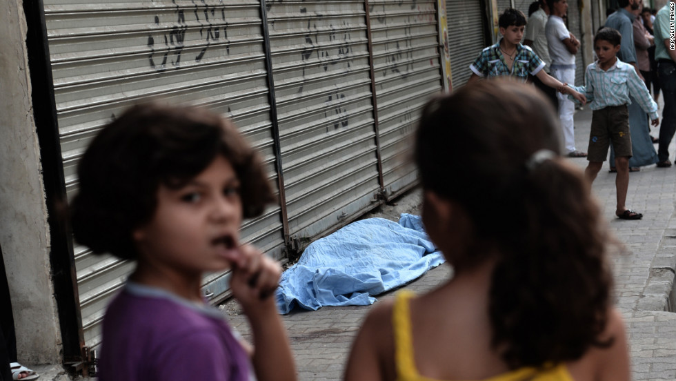 "Children pass a bagged body outside a hospital in  Aleppo on Thursday, August 30. Click through the gallery to view images of the fighting in August. <a href=""http://www.cnn.com/2012/10/09/world/gallery/syria-unrest-july/index.html"" target=""_blank"">See photographs of the fighting in July.</a>"