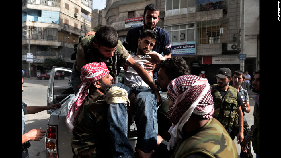 Members of the Syrian opposition carry a wounded man outside a hospital in Aleppo on Thursday, August 30.