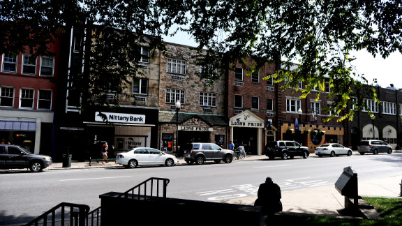 A man sits on College Avenue, the main drag that is lined by shops and restaurants.