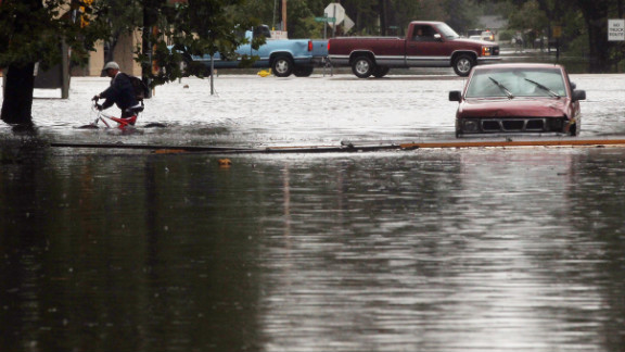 A resident evacuates an area flooded by Hurricane Isaac