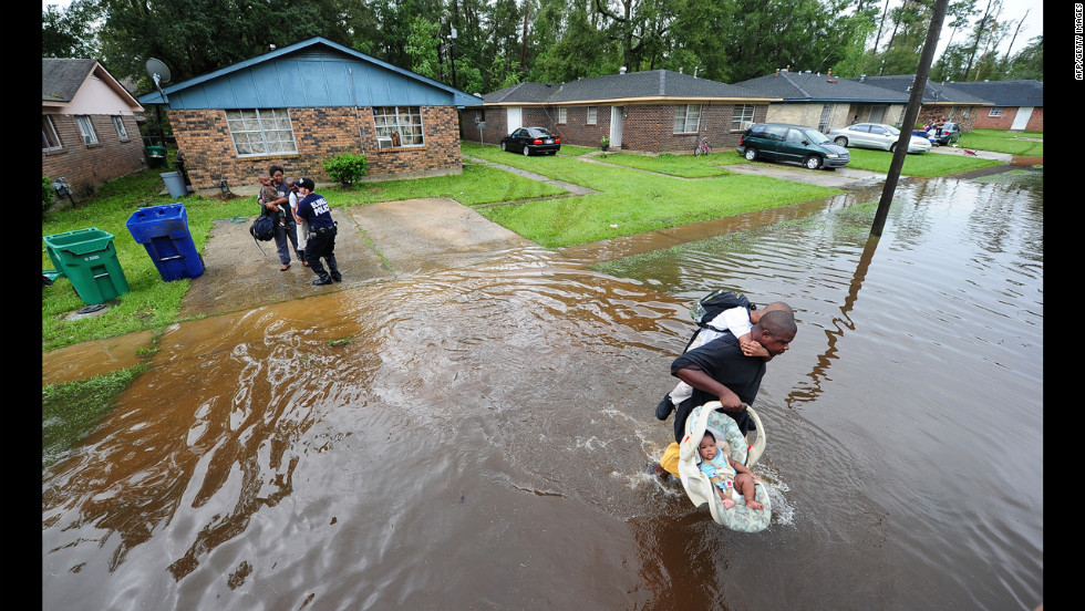 Jamaal Nelson carries his son, Jon-Wesley, 6, on his back and his 4-month-old baby daughter, Jalashia, while being evacuated from their flooded neighborhood in Slidell.