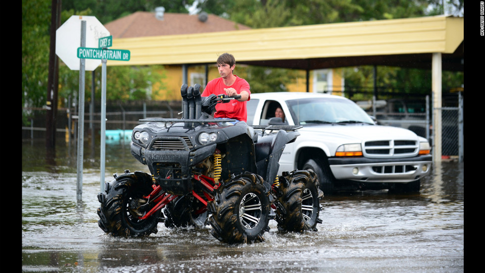 A man drives an off-road vehicle through flooded streets in Slidell.