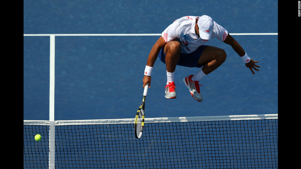 Jo-Wilfried Tsonga of France jumps over the net while trying to return a shot against Martin Klizan of Slovakia.
