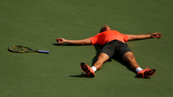 Nicolas Almagro of Spain lies on the court as he celebrates match point after his men