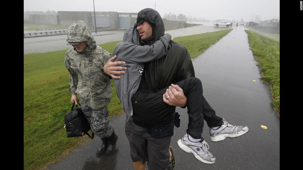 First responders carry people across the top of the levee from Plaquemines Parish to St. Bernard Parish.