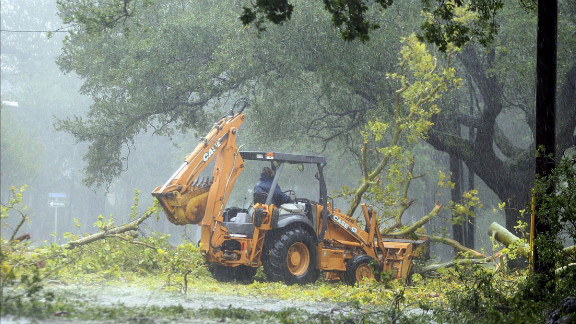 A worker in the driving rain tries to clear fallen limbs in the riverbound lanes of Espanade Avenue near McDonogh High School in New Orleans.