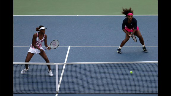 Sisters and doubles partners Venus Williams, left, and Serena Williams of the U.S. take on U.S. players Mallory Burdette and Nicole Gibbs during their women