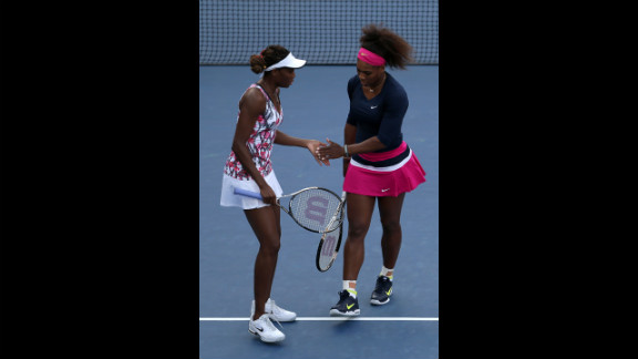 Venus Williams, left, and Serena Williams tap hands during their women