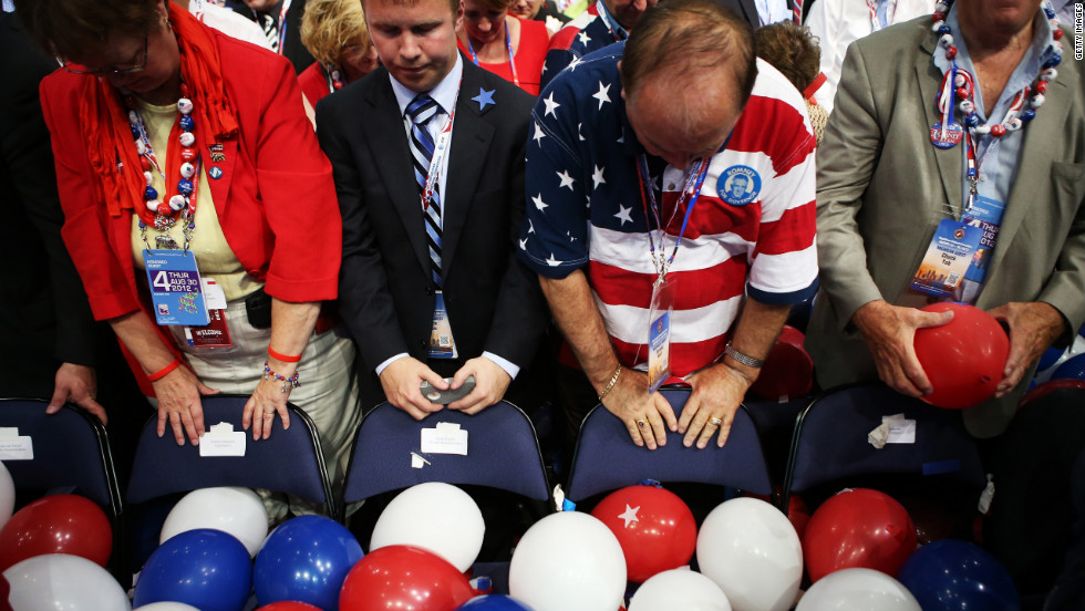 People bow their heads for the benediction to wrap up the GOP convention.