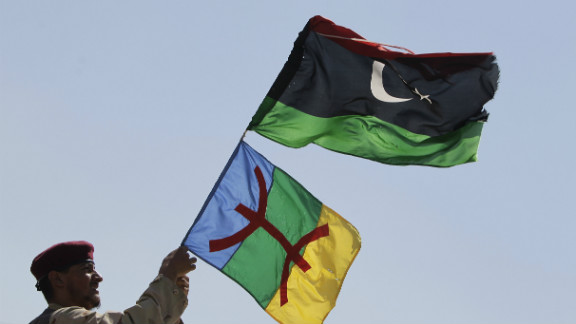 """A soldier waves Libyan and Amazigh flags on the frontline of battle against the remnants of the Gadhafi regime in September 2011. The red symbol on the Amazigh flag is the character for """"free man,"""" the name by which Berbers to themselves in Tamazight."""
