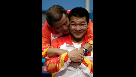 Chinese Qi Feng is congratulated by his coach Weipo Li for his gold during the medal ceremony of the Men