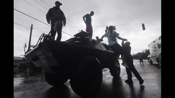 People get off a Slidell Police Department SWAT vehicle after being rescued from flooding from Isaac