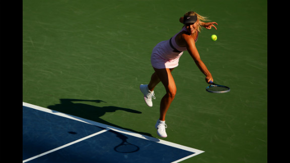 Maria Sharapova of Russia returns a shot against Mallory Burdette of the United States during their women
