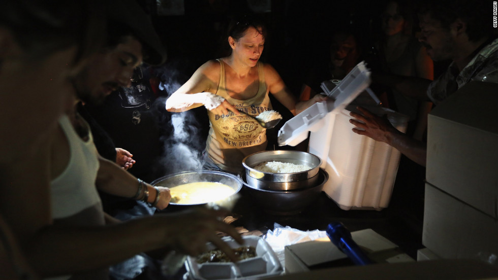 Local residents serve up chicken etouffee and rice delivered by the Louisiana National Guard at JJ's Bar in the Bywater neighborhood of New Orleans. The military gave out the food to residents of the area, which was still without electricity three days after Hurricane Isaac knocked out power to hundreds of thousands of people.