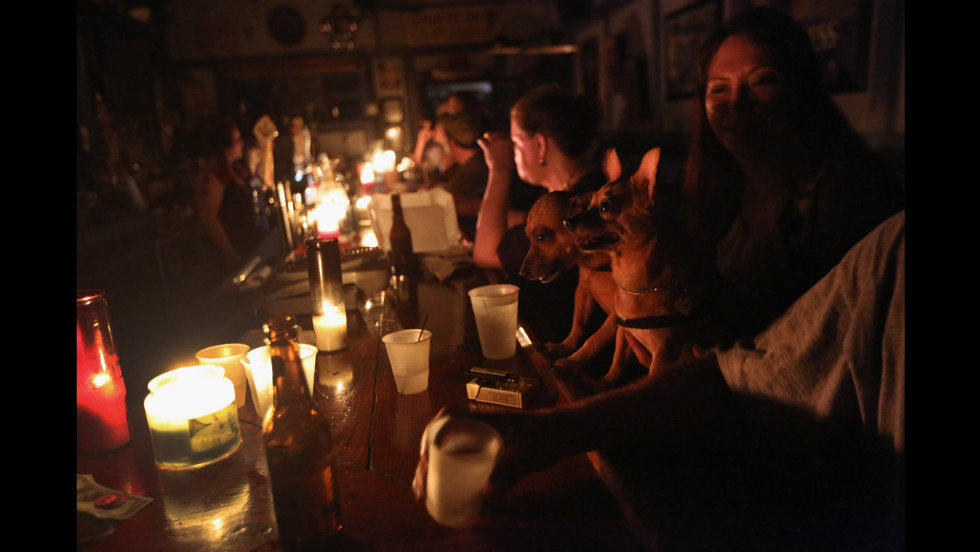 Local residents drink by candlelight at JJ's bar during the continued blackout.