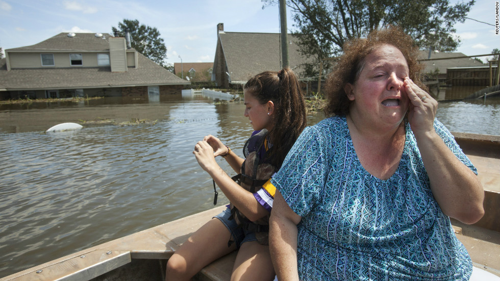 Plaquemines Parish resident Angela Serpas reacts after seeing her flooded home for the first time following Hurricane Isaac, as her daughter Lainy takes pictures, in Braithwaite, Louisiana, on Saturday, September 1.