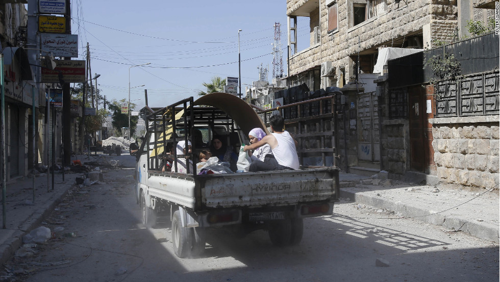 Escaping civilians drive through the El Amreeyeh neighborhood in Aleppo.