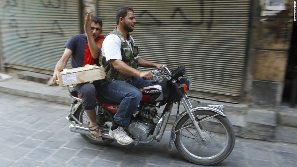 Free Syrian Army fighters transport explosives on a motorbike in Aleppo on Friday, August 31.