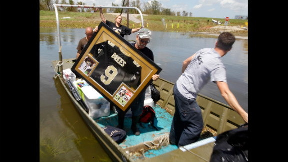 Russell Wilson, center, helps to move a water-damaged Drew Brees jersey from his daughter