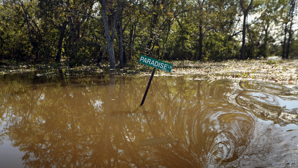 A Paradise Lane street sign is partially submerged in Isaac's floodwaters in Braithwaite, Louisiana, on Saturday, September 1.