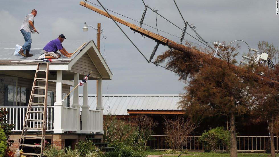Workers repair the roof of a home as downed power lines caused by Hurricane Isaac lean onto a tree in lower Plaquemines Parish on Sunday, September 2.
