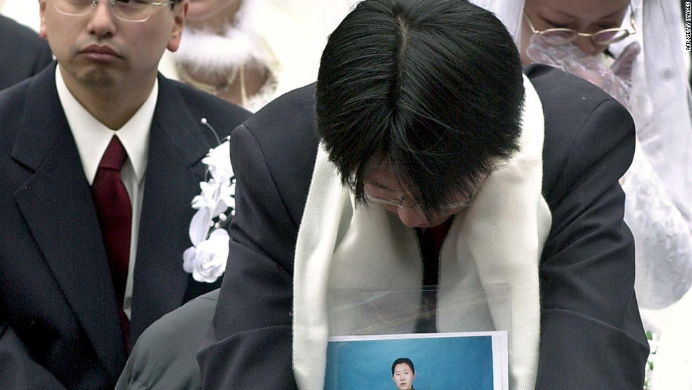 A Japanese devotee holds a portrait of his bride, who couldn't join in the mass wedding event at the Olympic Stadium in Seoul on February 13, 2000. Moon married some 30,000 couples at the event.