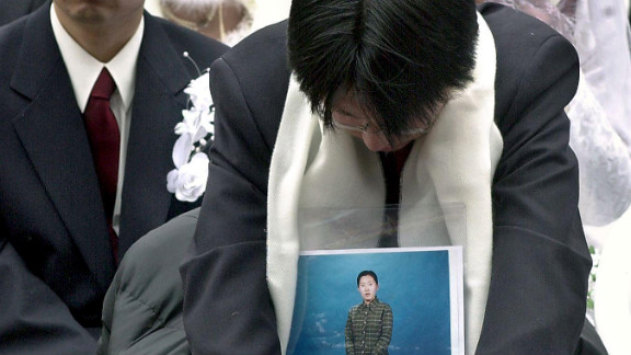 A Japanese devotee holds a portrait of his bride, who couldn
