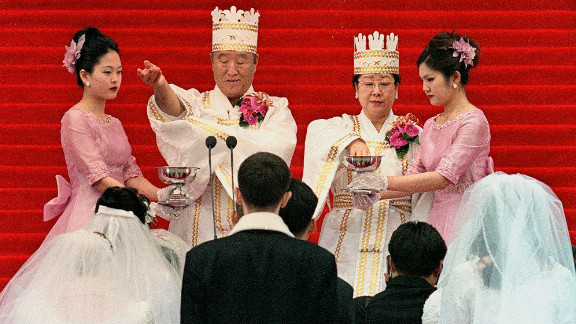 """Moon and his wife bless the brides and the grooms during the ceremony in Seoul. Followers of the Unification Church are sometimes referred to as """"Moonies."""""""