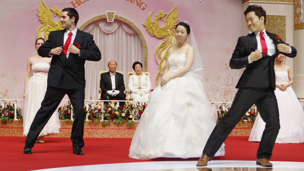 Moon and his wife, Hak Ja Han, watch the newly married couples dance a waltz.