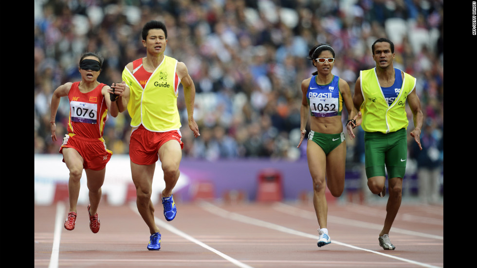 China's Jia Juntingxian, left, runs with her guide, Xu Dongloin, against Brazil's Jerusa Geber Santos and her guide, Luiz Henrique Barboza Da Silva, during the women's 200 meters T11 semifinal race.