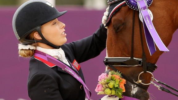 Sophie Wells of Great Britain caresses her horse Pinocchio after winning silver in the dressage individual championship test -Grade IV on Sunday.