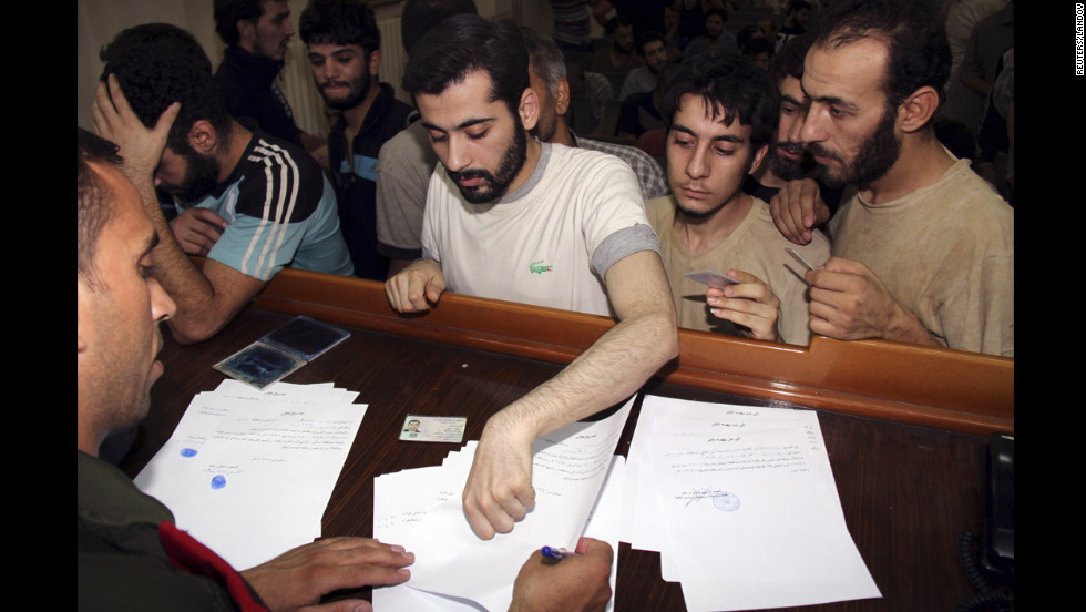 Syrian detainees who were arrested for participation in protests against Syrian President Bashar al-Assad's regime sign their release papers at the Damascus police leadership building Saturday, September 1.