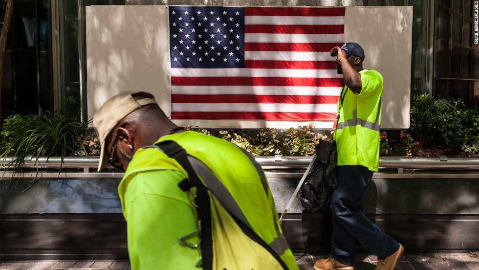 Street cleaners pass by the American flag in Charlotte on Sunday.