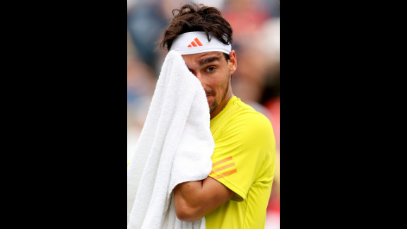 Fognini wipes his face with a towel during his men