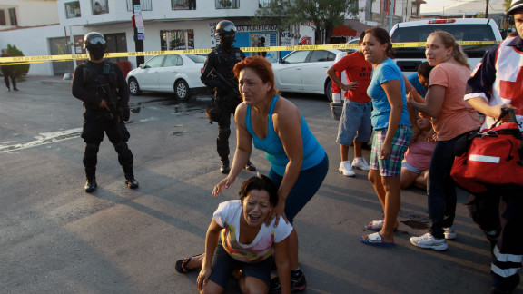 Family members grieve for victims at the scene of a triple homicide last week in Monterrey, Mexico.